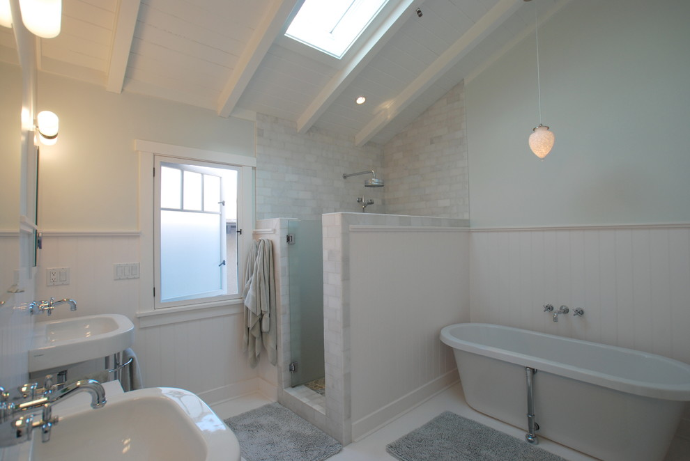 Inspiration for a tropical subway tile bathroom remodel in Orange County with a wall-mount sink and a hinged shower door