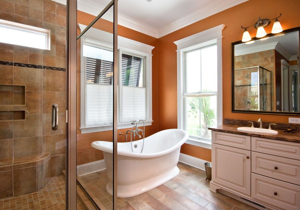 Example of a classic freestanding bathtub design in Charleston with granite countertops and orange walls