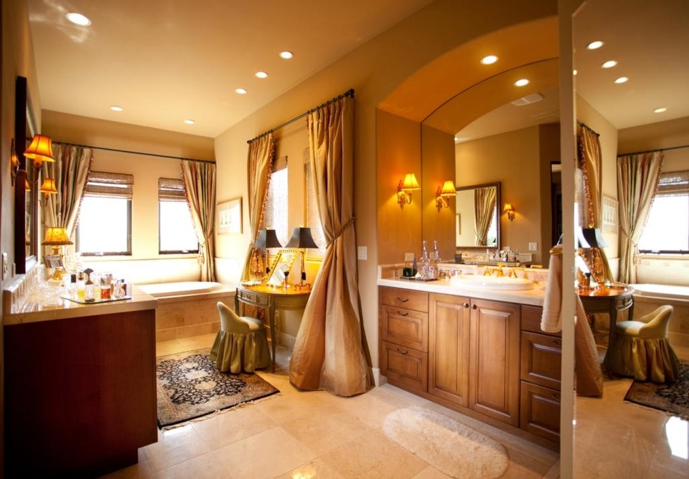 Elegant beige tile drop-in bathtub photo in Denver with a vessel sink, raised-panel cabinets and medium tone wood cabinets
