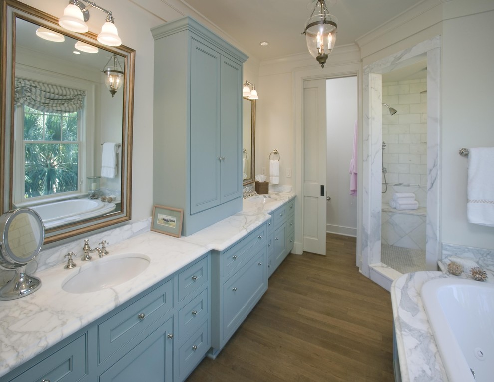 Inspiration for a timeless corner shower remodel in Charleston with blue cabinets