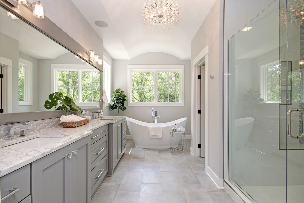 Transitional master gray floor bathroom photo in Grand Rapids with shaker cabinets, gray cabinets, gray walls, an undermount sink, a hinged shower door and white countertops