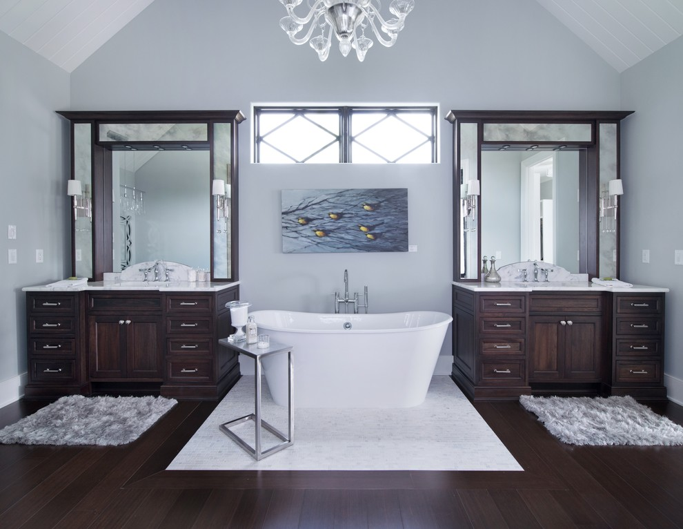 Freestanding bathtub - huge transitional white tile and stone slab bamboo floor freestanding bathtub idea in Kansas City with an undermount sink, recessed-panel cabinets, dark wood cabinets, marble countertops, a two-piece toilet and gray walls