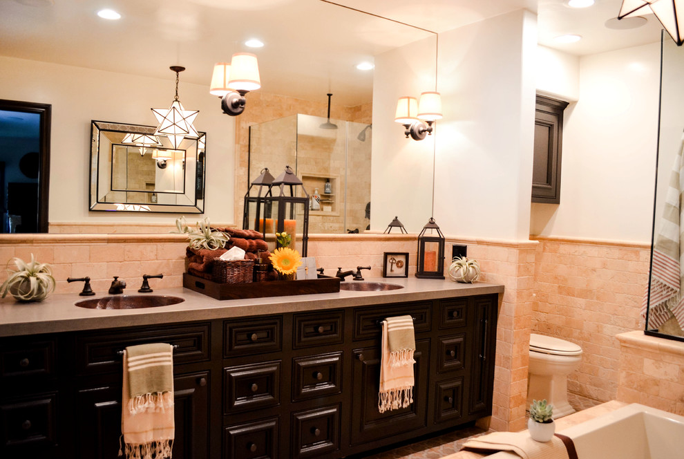 Mid-sized tuscan master beige tile and travertine tile porcelain tile and multicolored floor bathroom photo in Los Angeles with beaded inset cabinets, brown cabinets, a one-piece toilet, white walls, an undermount sink, solid surface countertops, a hinged shower door and gray countertops