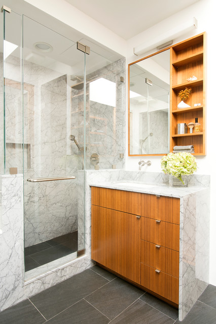 Medium sized contemporary bathroom in New York with flat-panel cabinets, medium wood cabinets, a corner shower, a one-piece toilet, grey tiles, stone slabs, white walls, porcelain flooring, a submerged sink, marble worktops and a hinged door.