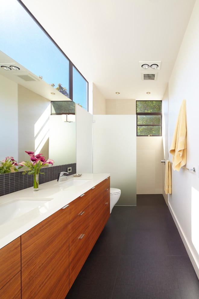 Trendy master black tile walk-in shower photo in San Francisco with an undermount sink, flat-panel cabinets, medium tone wood cabinets, quartz countertops, a one-piece toilet and white walls