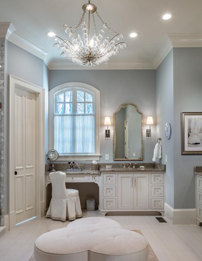 アトランタの広いトラディショナルスタイルのおしゃれなマスターバスルーム (ベージュのキャビネット、グレーの壁、磁器タイルの床、アンダーカウンター洗面器、珪岩の洗面台、ベージュの床、落し込みパネル扉のキャビネット、グレーの洗面カウンター) の写真