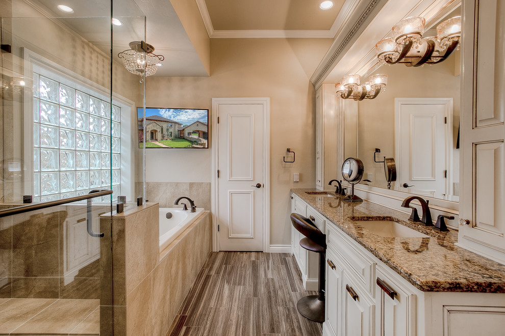 Inspiration for a timeless master beige tile bathroom remodel in Oklahoma City with an undermount sink and raised-panel cabinets