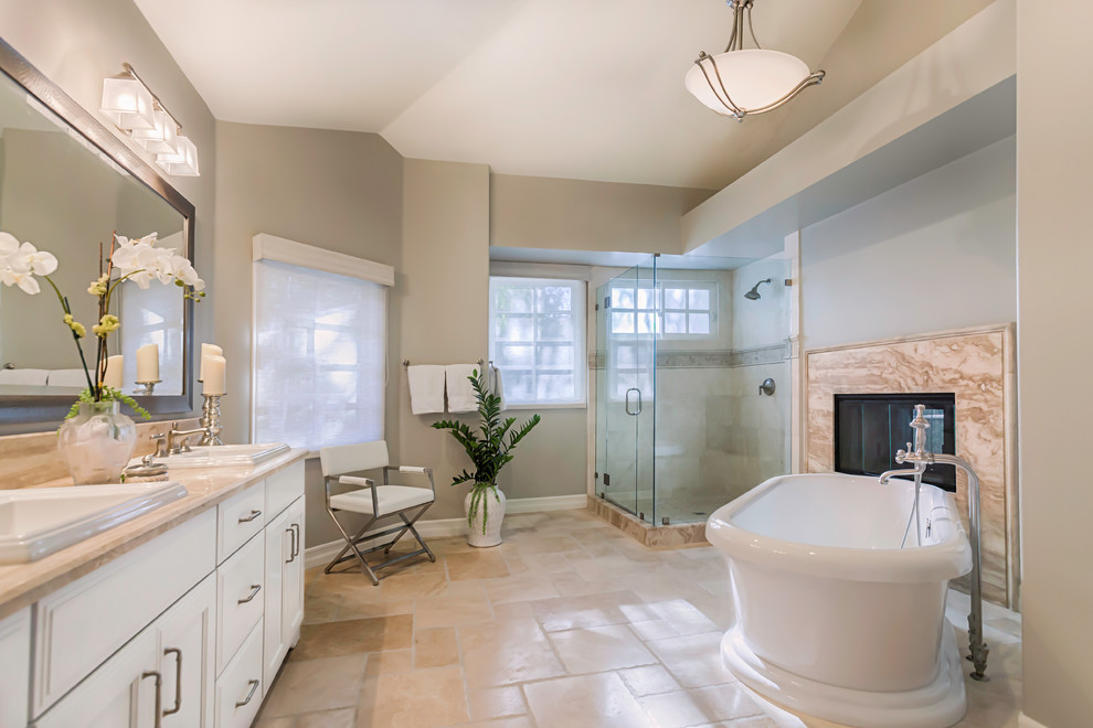 Example of a large transitional master beige tile and travertine tile travertine floor and beige floor bathroom design in Los Angeles with a drop-in sink, white cabinets, beige walls, recessed-panel cabinets, marble countertops and a hinged shower door