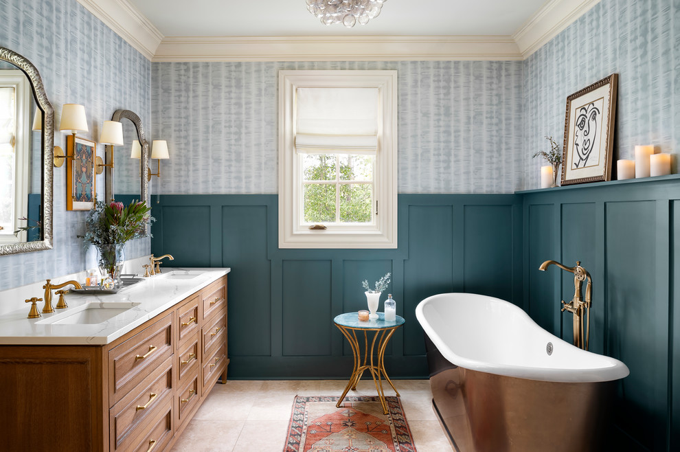 Example of a classic ceramic tile and beige floor freestanding bathtub design in Atlanta with furniture-like cabinets, light wood cabinets, an undermount sink, quartz countertops and white countertops