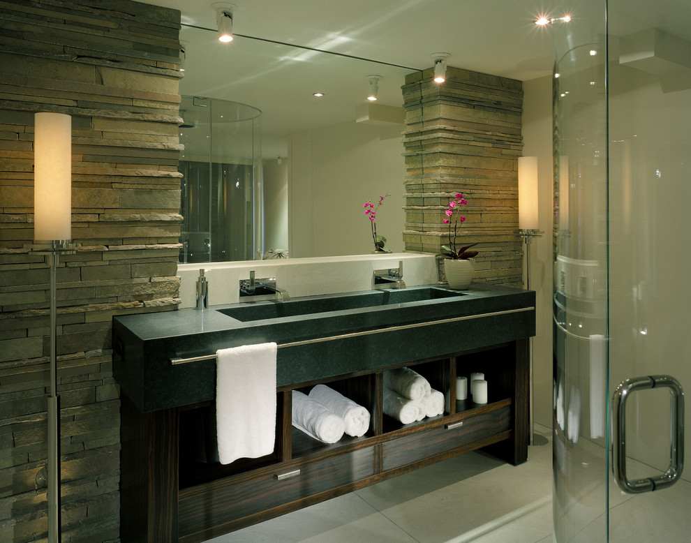 Mid-sized trendy master gray tile and stone tile concrete floor and gray floor corner shower photo in Seattle with a trough sink, open cabinets, dark wood cabinets, gray walls, concrete countertops, a hinged shower door and gray countertops