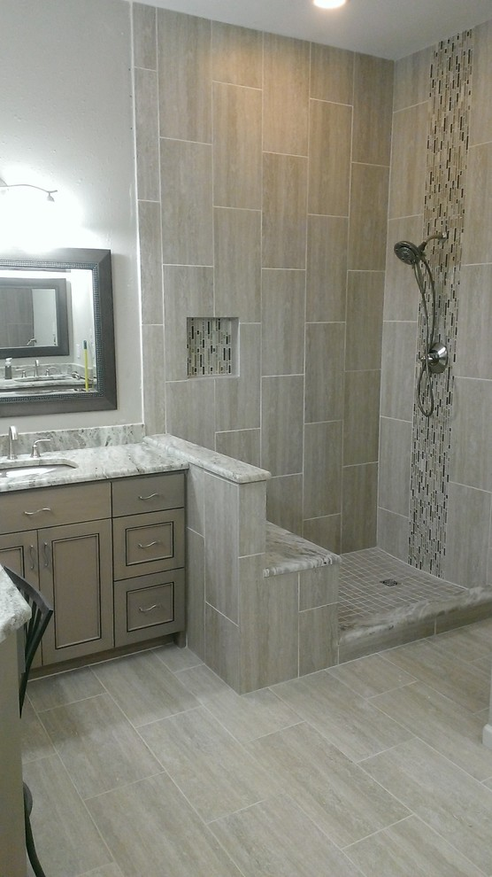 Mid-sized trendy master gray tile and porcelain tile porcelain tile corner shower photo in Austin with an undermount sink, recessed-panel cabinets, gray cabinets, marble countertops and gray walls