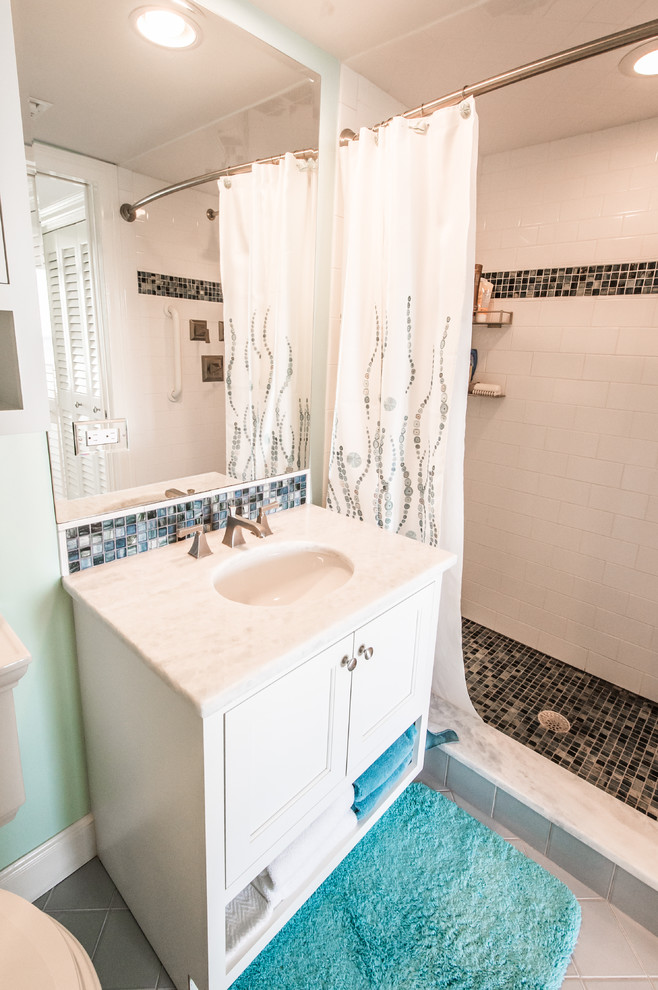 Example of a mid-sized beach style 3/4 beige tile, black and white tile, brown tile and mosaic tile alcove shower design in Miami with recessed-panel cabinets, white cabinets, a two-piece toilet, green walls, an undermount sink and granite countertops