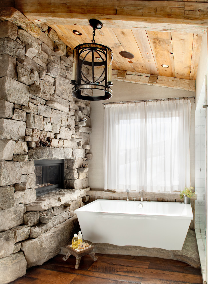 Inspiration for a rustic stone slab medium tone wood floor freestanding bathtub remodel in Other with beige walls and marble countertops