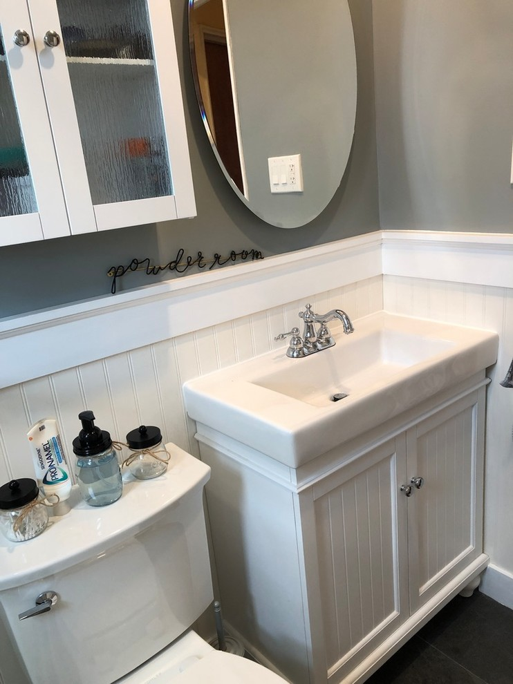 Bathroom - mid-sized transitional master white tile and ceramic tile porcelain tile and gray floor bathroom idea in New York with furniture-like cabinets, white cabinets, a two-piece toilet, gray walls, an integrated sink, solid surface countertops and white countertops