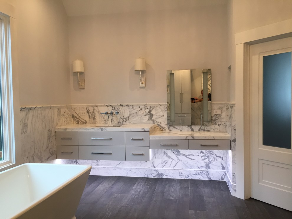 Inspiration for a large timeless master black and white tile and marble tile porcelain floor and brown floor bathroom remodel in New York with flat-panel cabinets, white cabinets, a one-piece toilet, gray walls, an undermount sink, marble countertops and white countertops