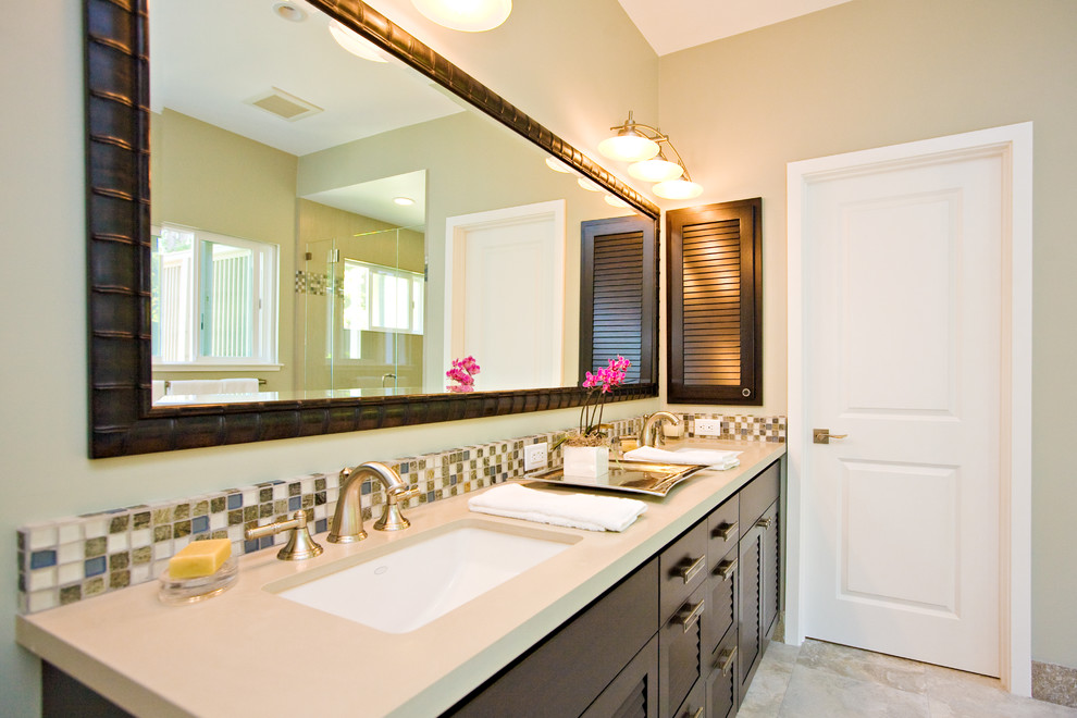 Example of a large island style brown tile limestone floor bathroom design in San Francisco with a drop-in sink, louvered cabinets, dark wood cabinets, solid surface countertops, a one-piece toilet and gray walls