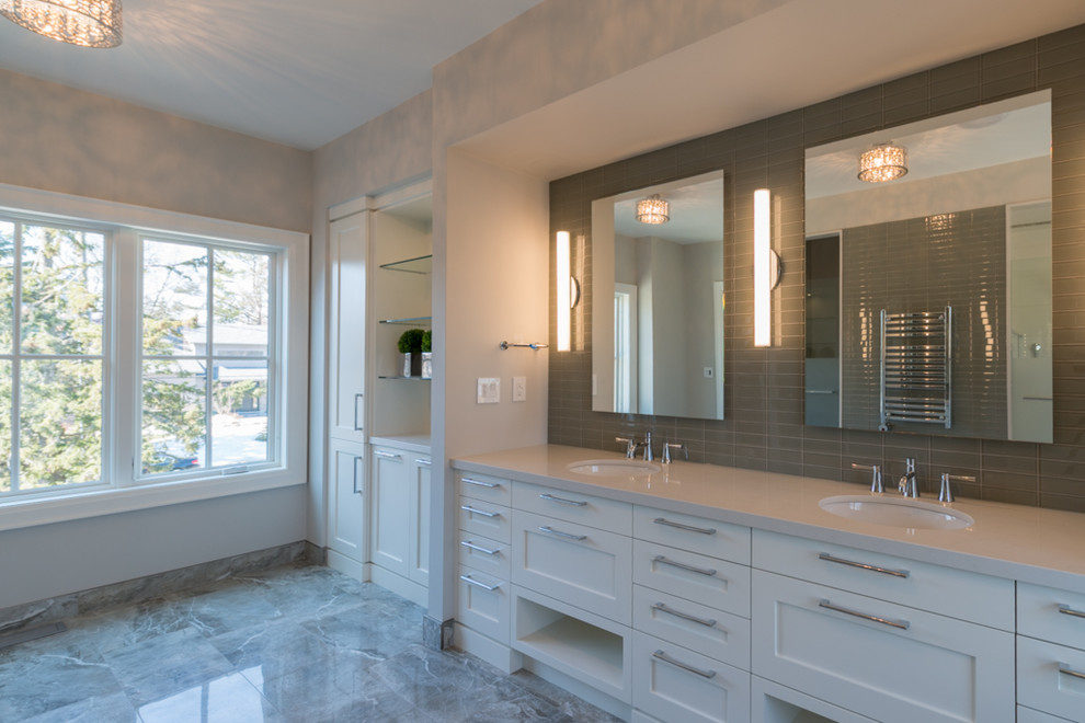 Example of a large trendy master gray tile and porcelain tile porcelain tile bathroom design in Toronto with an undermount sink, shaker cabinets, white cabinets, solid surface countertops, a one-piece toilet and gray walls