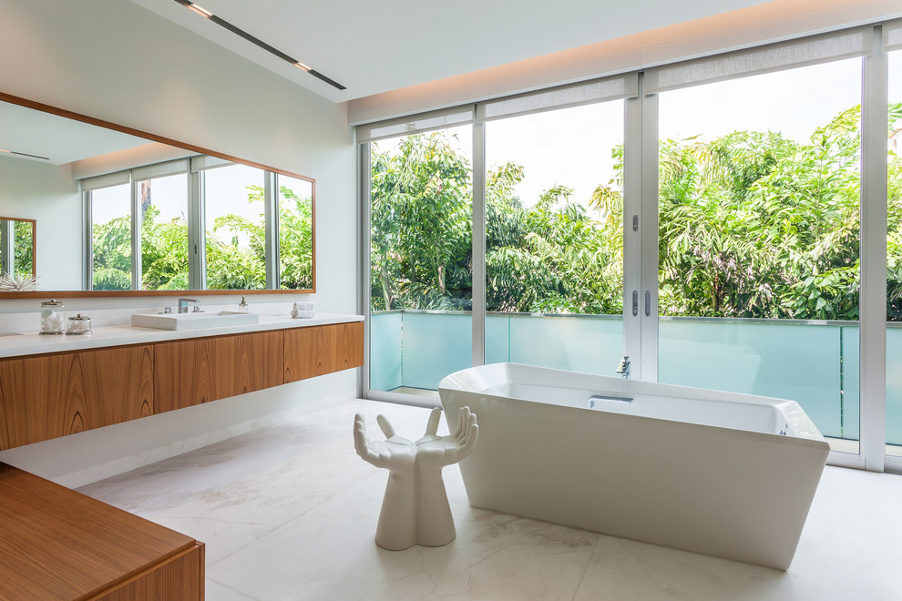 Example of a trendy freestanding bathtub design in Miami with a drop-in sink, flat-panel cabinets, medium tone wood cabinets and white walls