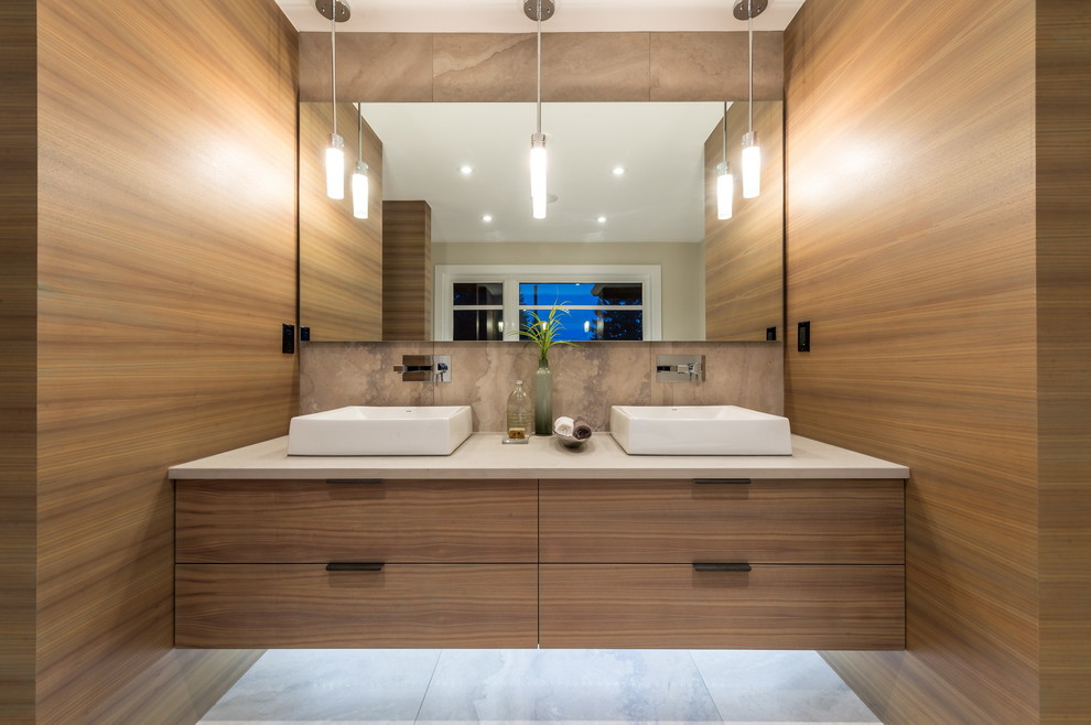 Inspiration for a large contemporary master beige tile and stone tile marble floor freestanding bathtub remodel in Vancouver with flat-panel cabinets, light wood cabinets, a vessel sink and solid surface countertops