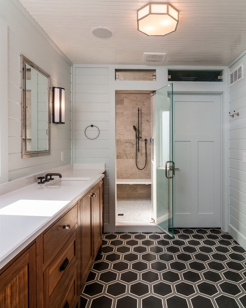 Large transitional master brown tile and travertine tile linoleum floor and black floor alcove shower photo in Other with shaker cabinets, medium tone wood cabinets, white walls, an undermount sink, a hinged shower door and solid surface countertops