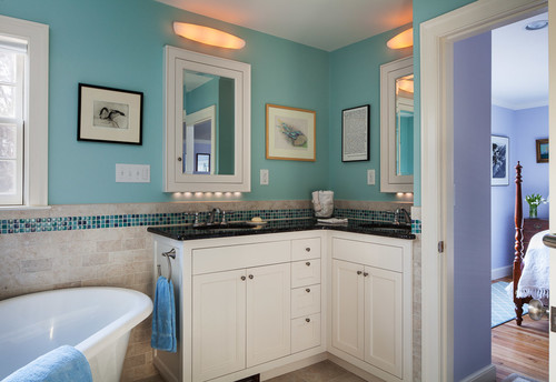 The bright robin's egg blue of this bathroom is complemented by the toned down cabinetry and pitch black countertops on the corner vanity.