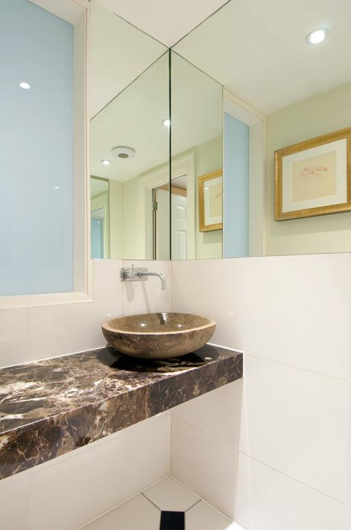 Foto de cuarto de baño único, contemporáneo, pequeño, con sanitario de pared, baldosas y/o azulejos blancos, baldosas y/o azulejos de cerámica, paredes blancas, suelo de baldosas de cerámica, lavabo sobreencimera, encimera de mármol, suelo multicolor y encimeras marrones