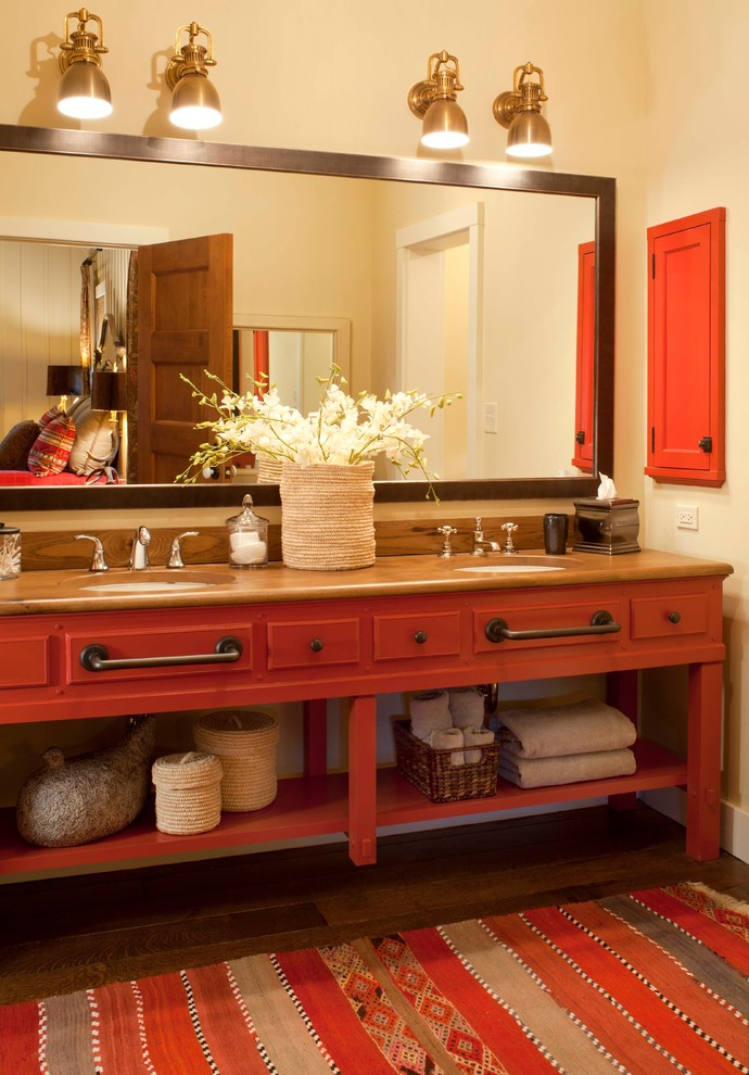 Inspiration for a rustic dark wood floor bathroom remodel in Denver with wood countertops, red cabinets, an undermount sink and brown countertops