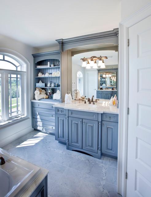 Esempio di una stanza da bagno chic con lavabo sottopiano, ante con bugna sagomata, ante blu, vasca da incasso e pareti grigie