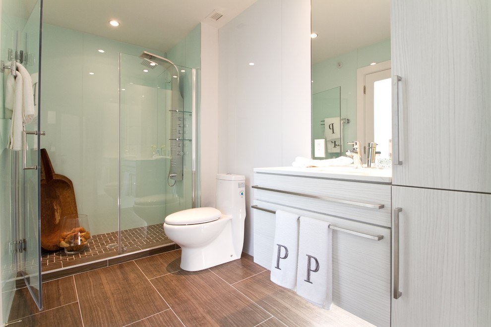Trendy ceramic tile alcove shower photo in Philadelphia with flat-panel cabinets, gray cabinets and a one-piece toilet
