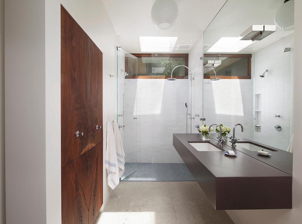 Diseño de cuarto de baño actual, de tamaño medio, con lavabo bajoencimera, ducha empotrada, baldosas y/o azulejos blancos, paredes blancas, suelo de cemento, aseo y ducha y puertas de armario de madera en tonos medios