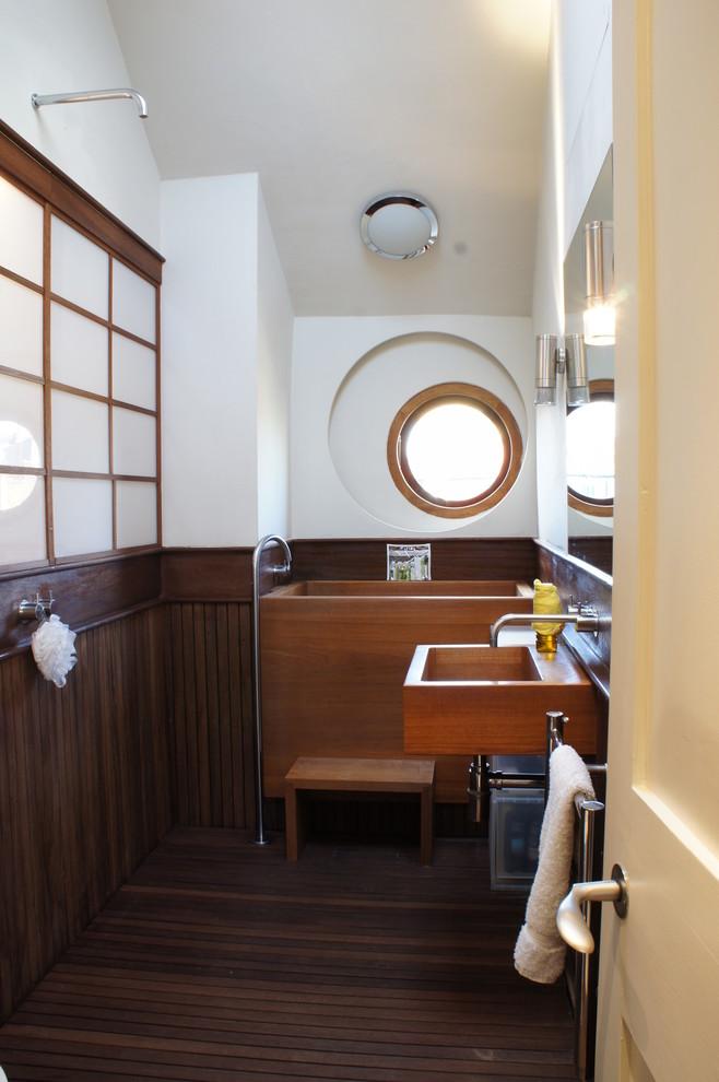 Bathroom - eclectic medium tone wood floor bathroom idea in London with a wall-mount sink and white walls
