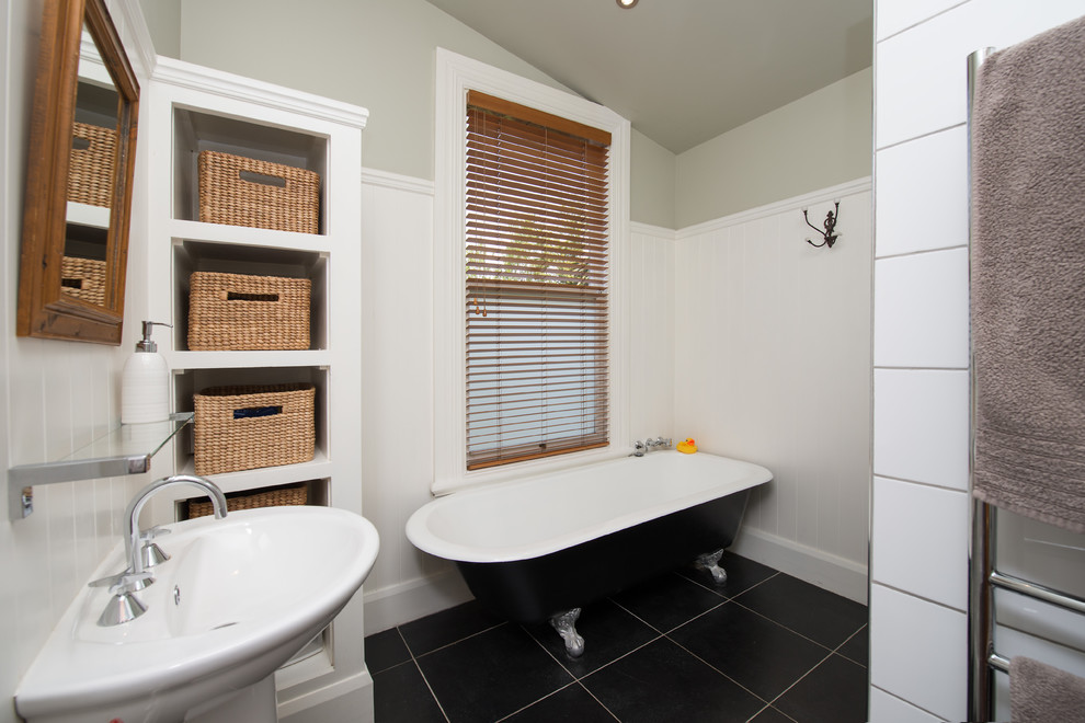 Inspiration for a traditional bathroom in Christchurch with a claw-foot tub, an alcove shower, black tile, ceramic tile, white walls, ceramic floors and a pedestal sink.
