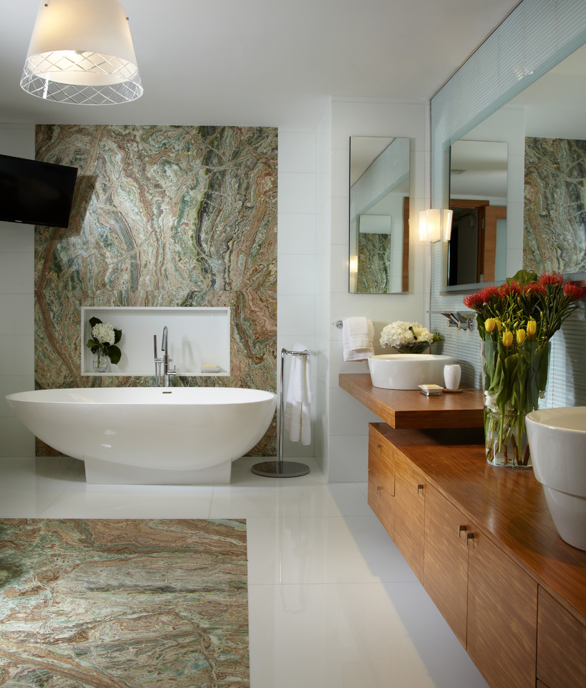 Freestanding bathtub - contemporary white tile freestanding bathtub idea in Miami with a vessel sink, flat-panel cabinets and medium tone wood cabinets