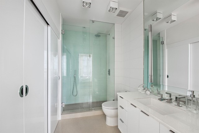 Inspiration for a mid-sized contemporary 3/4 porcelain tile porcelain tile alcove shower remodel in Miami with flat-panel cabinets, white cabinets, white walls, an undermount sink and quartz countertops