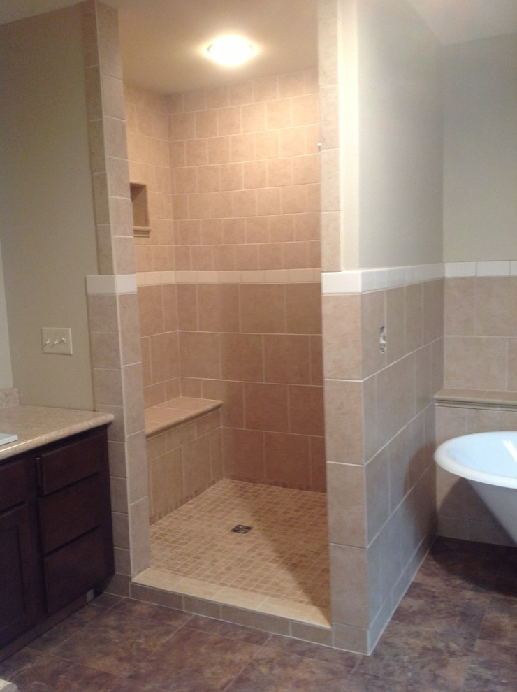 Example of a mid-sized classic brown tile and ceramic tile ceramic tile bathroom design in Other with a drop-in sink, recessed-panel cabinets, dark wood cabinets, laminate countertops, a one-piece toilet and beige walls