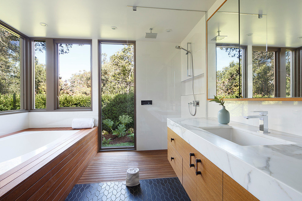 Mid-sized mid-century modern master medium tone wood floor and black floor bathroom photo in San Francisco with an undermount sink, flat-panel cabinets, an undermount tub, white walls, light wood cabinets and marble countertops
