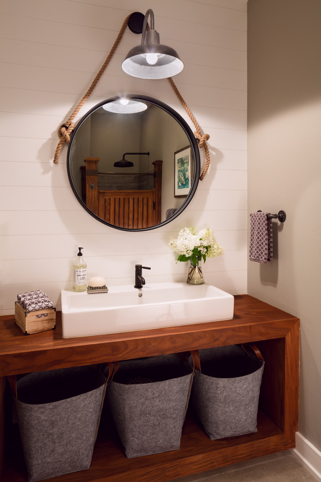 Example of a country bathroom design in Milwaukee with open cabinets, dark wood cabinets, beige walls and a trough sink