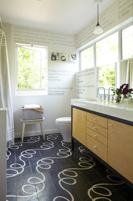 Example of a trendy black tile bathroom design in San Francisco with an integrated sink, flat-panel cabinets, light wood cabinets and white countertops