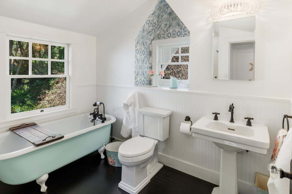 Transitional dark wood floor and brown floor claw-foot bathtub photo in San Francisco with white walls and a pedestal sink