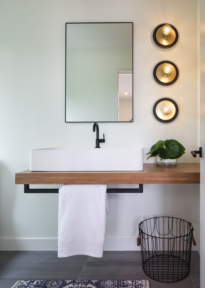 Small trendy porcelain tile and gray floor bathroom photo in Minneapolis with white walls, a vessel sink and wood countertops
