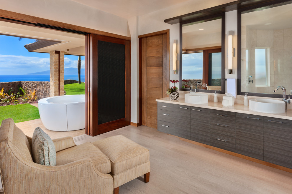 Inspiration for a large contemporary master beige floor and porcelain tile wet room remodel in Hawaii with flat-panel cabinets, a hot tub, a vessel sink, dark wood cabinets, white walls and limestone countertops