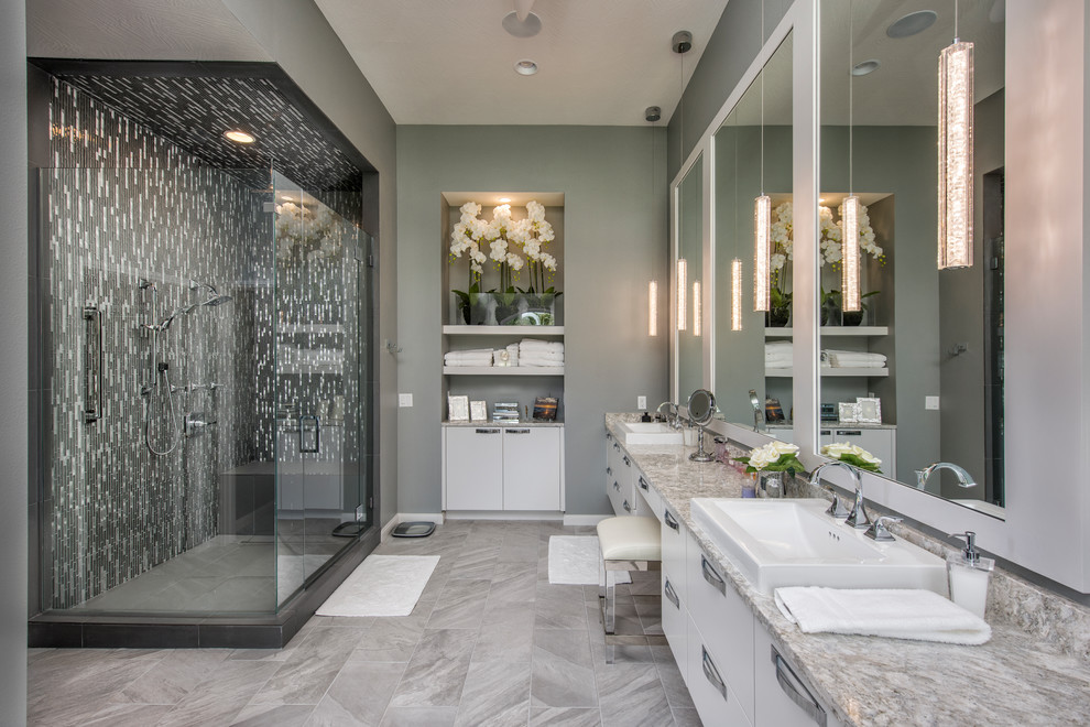 Trendy master multicolored tile and matchstick tile gray floor bathroom photo in Other with white cabinets, flat-panel cabinets, gray walls and a hinged shower door