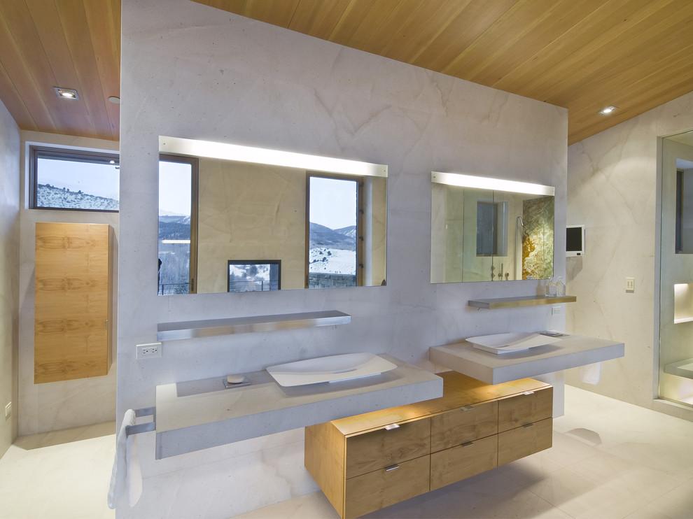 Modernes Badezimmer mit Aufsatzwaschbecken, flächenbündigen Schrankfronten, Beton-Waschbecken/Waschtisch und hellen Holzschränken in Denver