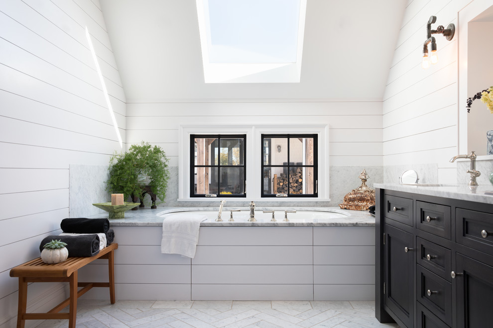 Example of a mid-sized farmhouse master white floor bathroom design in New York with recessed-panel cabinets, black cabinets, an undermount tub, white walls and gray countertops