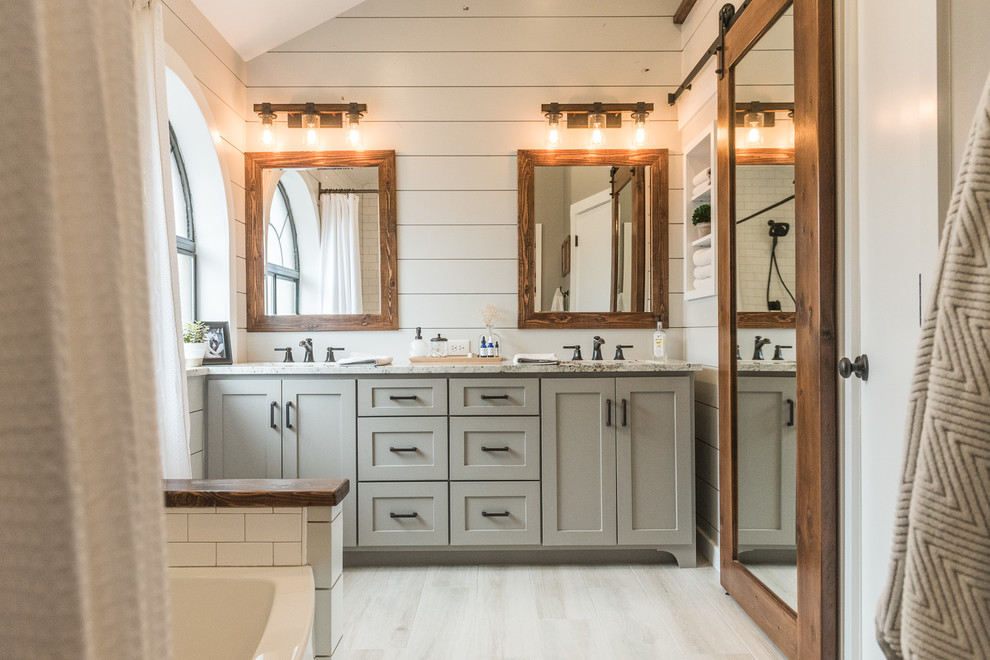 Example of a mid-sized farmhouse master gray tile and porcelain tile porcelain tile bathroom design in Dallas with shaker cabinets, gray cabinets, a one-piece toilet, gray walls, an undermount sink and granite countertops
