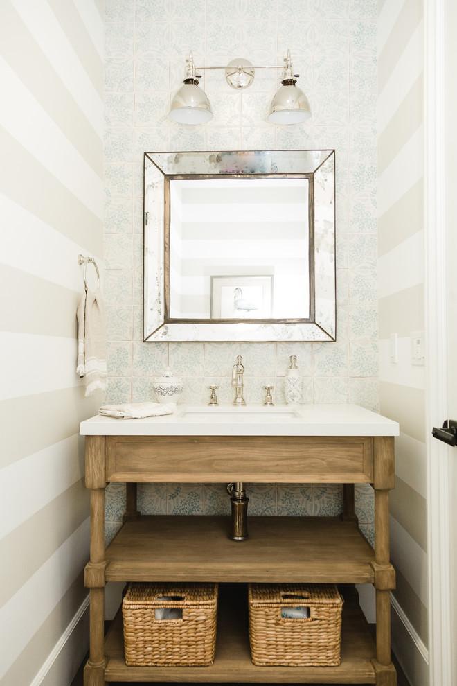 サンディエゴのビーチスタイルのおしゃれな浴室 (家具調キャビネット、中間色木目調キャビネット、青いタイル、白いタイル、マルチカラーの壁、アンダーカウンター洗面器、白い洗面カウンター) の写真