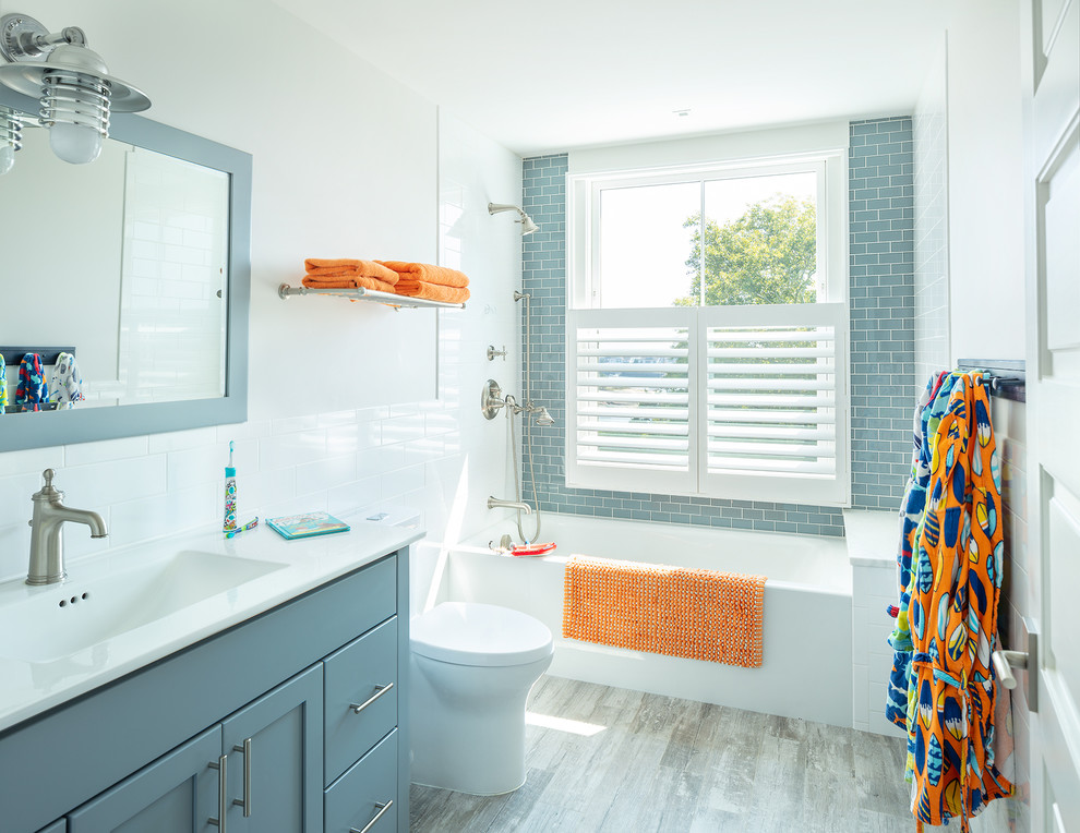 Inspiration for a mid-sized coastal kids' blue tile and subway tile porcelain tile and gray floor bathroom remodel in Other with shaker cabinets, blue cabinets, white walls, an integrated sink, white countertops, a one-piece toilet and solid surface countertops