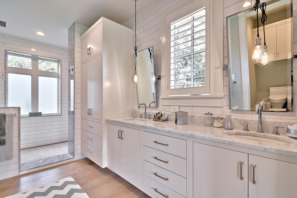 Example of a farmhouse subway tile bathroom design in Austin with marble countertops and an undermount sink