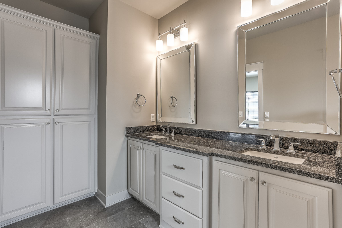 Example of a farmhouse master gray tile ceramic tile and gray floor doorless shower design in Omaha with raised-panel cabinets, white cabinets, a two-piece toilet, gray walls, an undermount sink, gran