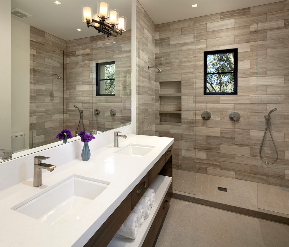 Example of a large tuscan master gray tile and stone tile porcelain tile alcove shower design in Santa Barbara with an undermount sink, flat-panel cabinets, dark wood cabinets, white walls and solid surface countertops